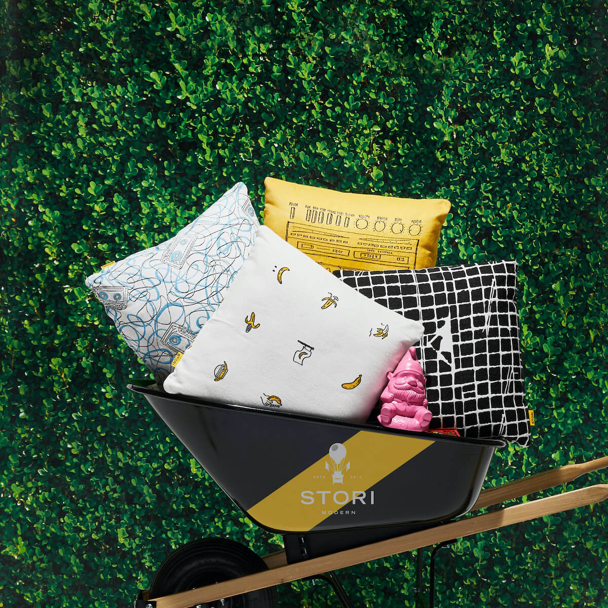 stori modern outdoor throw pillows in a wheel barrow