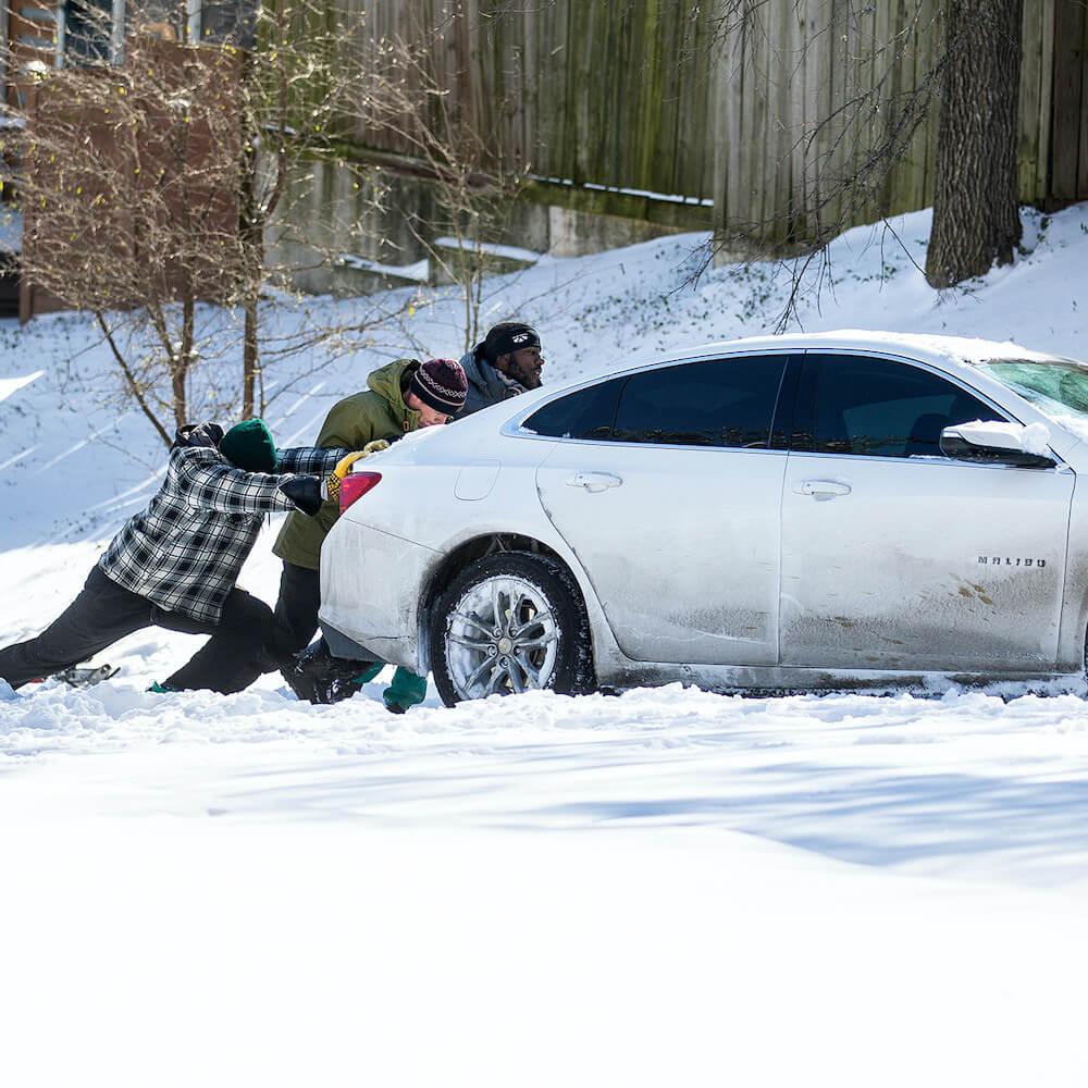 People pushing a car in snow