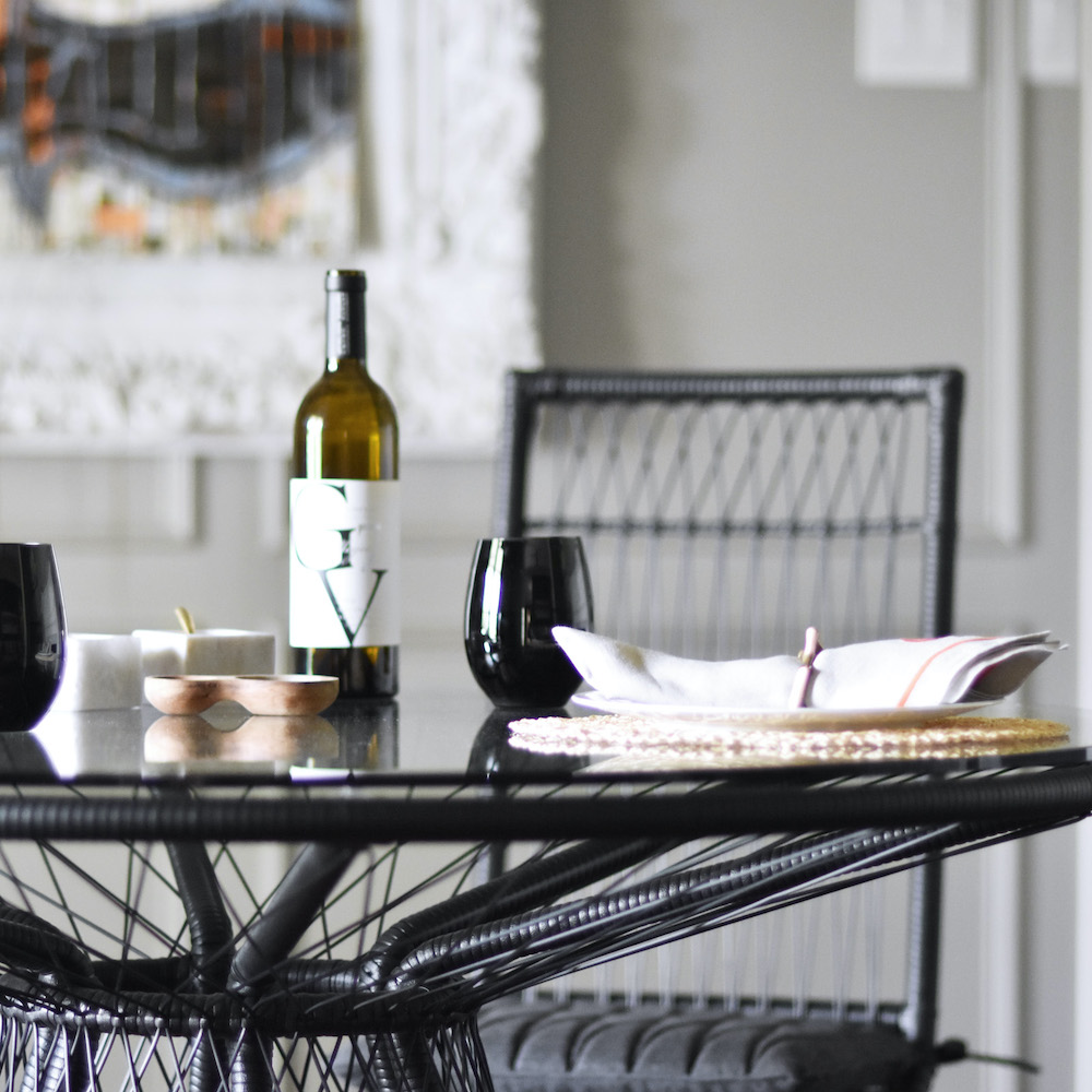 Stori Modern Memoir Outdoor Woven table in black with a bottle of wine