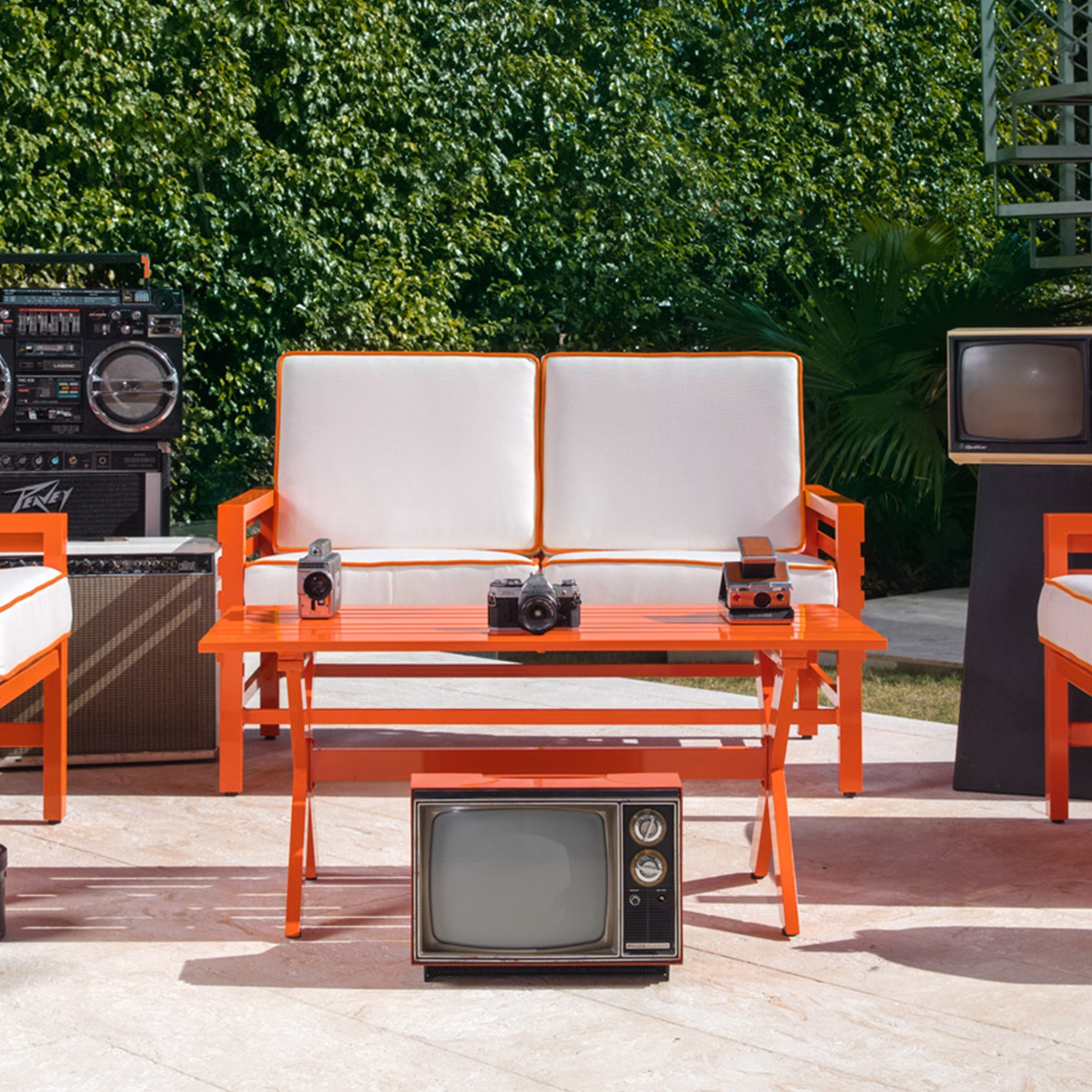 Stori Modern Graphic Collection in orange with white cushions surrounded by vintage electronics.
